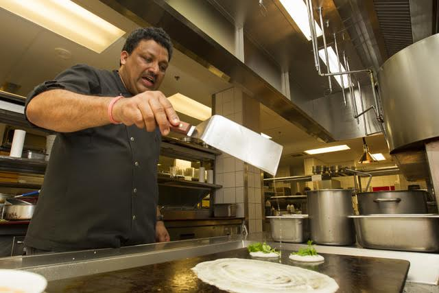 CINDY ELLEN RUSSELL / CRUSSELL@STARADVERTISER.COM Halekulani executive chef Vikram Garg adds batter to the grill to make rice and lentil pancakes called uttapam, as well as a larger crepe made from the same batter. Various fresh toppings give uttapam a pizzalike look.